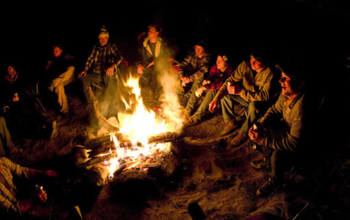 description: The cast and crew enjoy the evening's campfire.